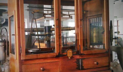 """""""As probas pesan máis na balanza que os máis elocuentes discursos"""" (John Ruskin).  Balanza de precisión mercada no 1890."""